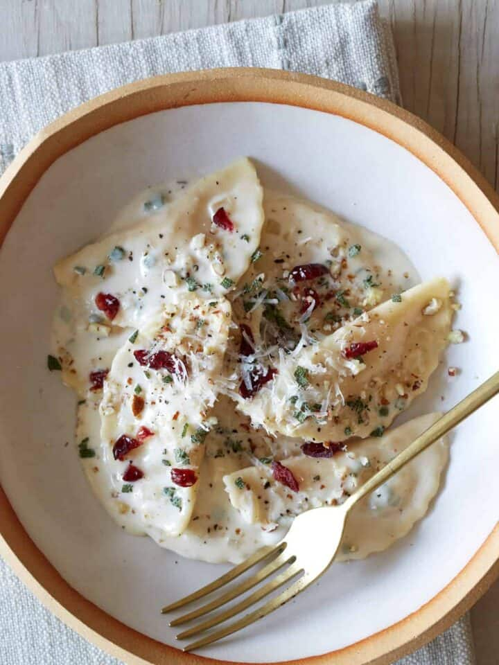 A bowl of butternut squash mezzaluna with roasted garlic sage cream sauce and a fork.