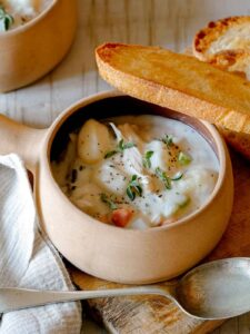 A soup bowl with handle of creamy chicken and gnocchi soup with bread and a spoon.