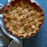 A whole maple, pear, ginger pie with linens and a pie server.