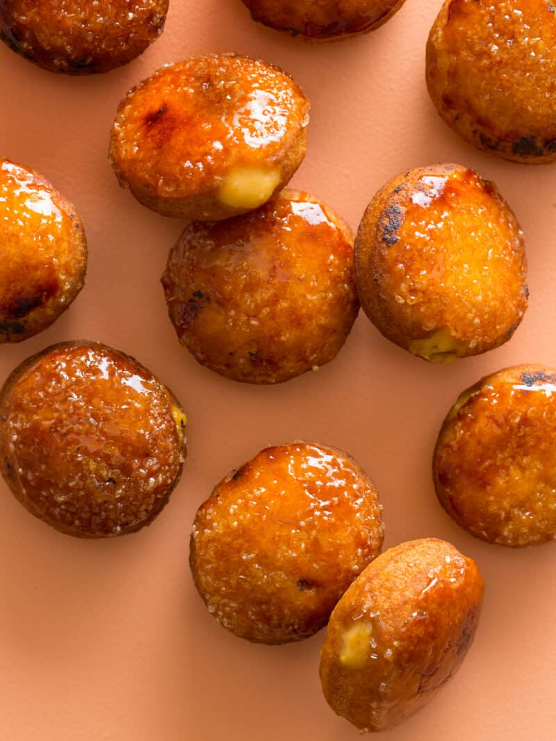 Pumpkin Creme Brulled donuts on an orange surface.