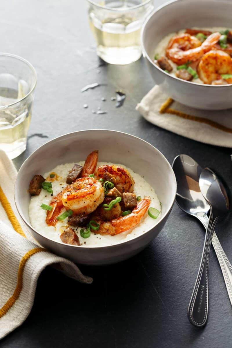Bowls of shrimp and grits with spoons.