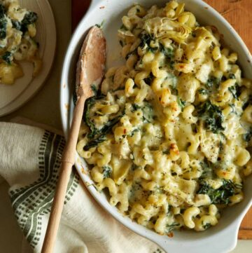 A baking pan of spinach artichoke mac and cheese with a wooden spoon.