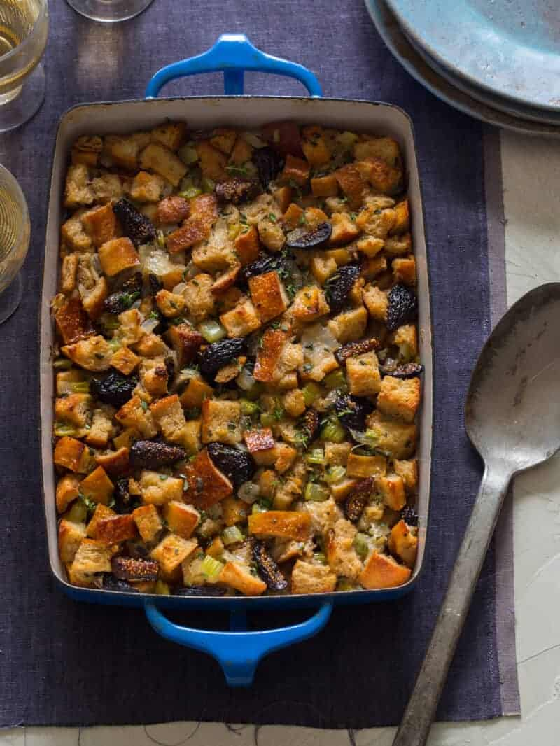A pan of fig, herb, and sausage stuffing with a serving spoon.