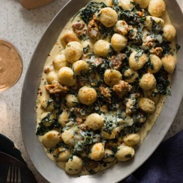 Sausage and kale baked gnocchi on an oval platter.