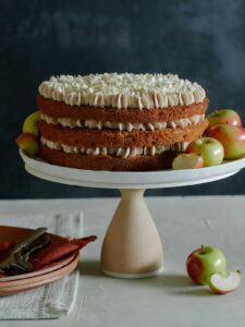 A whole apple cake with chai spiced buttercream on a cake stand with apples and plates.