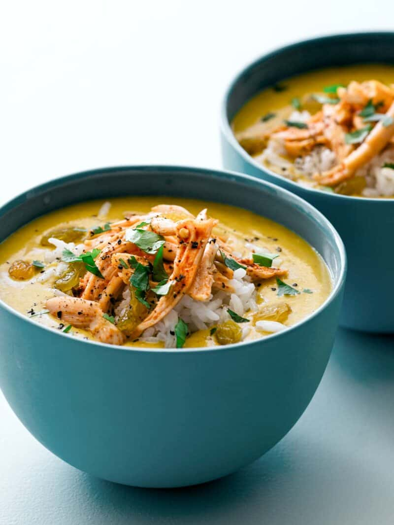 Close up of our Mulligatawny soup recipe topped with rice, chicken, golden raisins and cilantro.