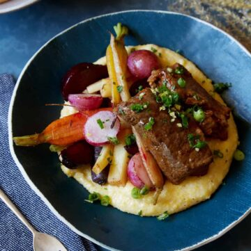 A bowl of white wine braised short ribs with vegetables over white cheddar polenta.