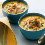 Bowls of one pot chicken mulligatawny soup with a spoon.