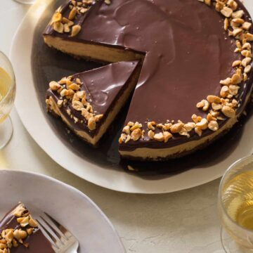 A sliced no bake peanut butter cheesecake with dark chocolate ganache with plates served.