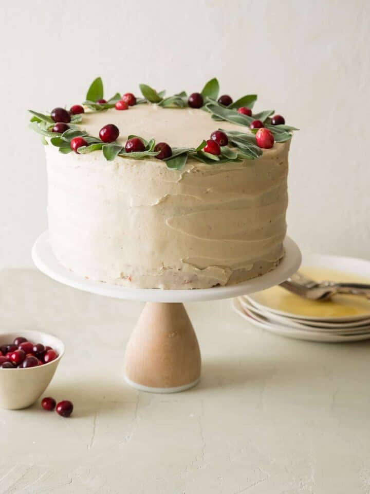 Apple cranberry cake with brown sugar buttercream decorated with fresh cranberries with plates and forks.