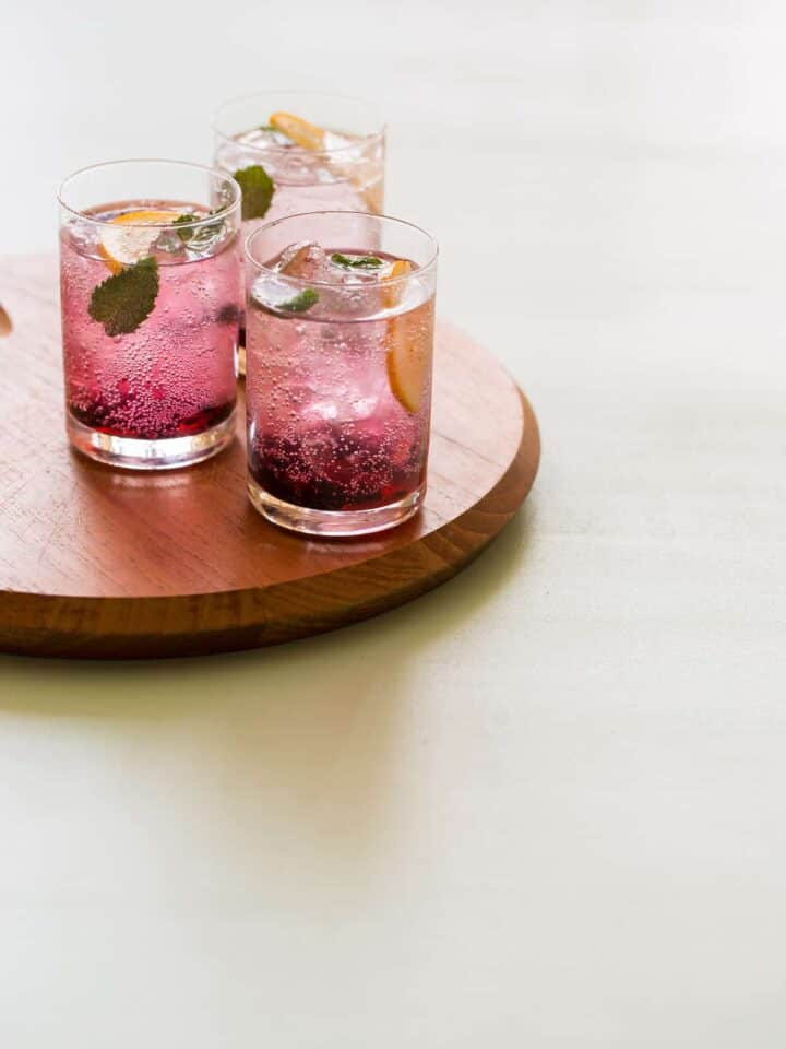 Glasses of blackberry and meyer lemon gin and tonics on a wooden board.