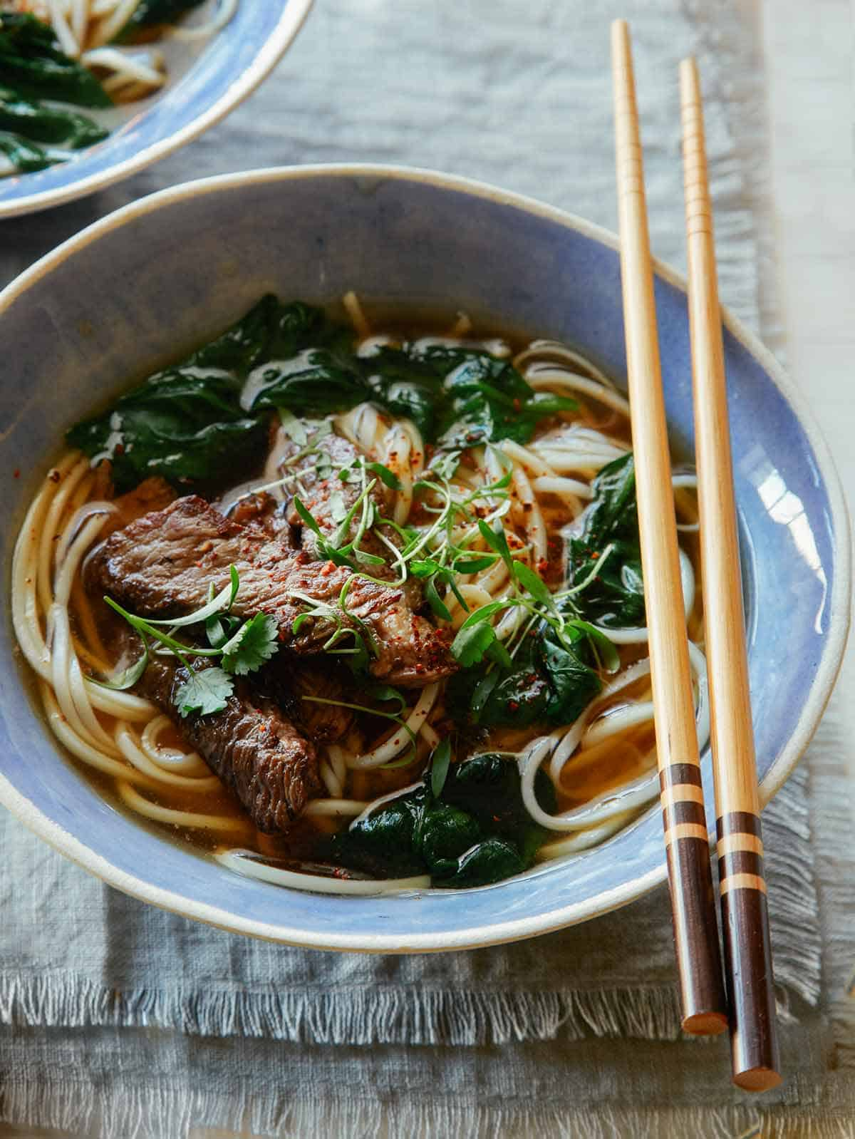 Beef noodle soup in a bowl with chopsticks.