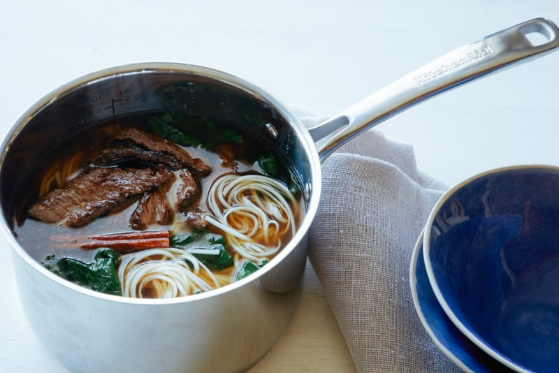 A pot of garlic ginger beef noodle soup with linens and blue bowls.