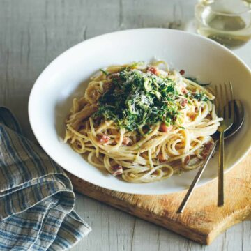 A bowl of creamy garlic pancetta spaghetti with crispy shredded brussels sprouts.