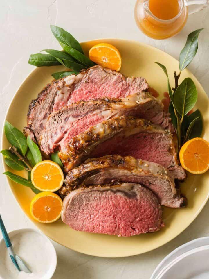 A plate of sliced standing rib roast garnished with orange halves.