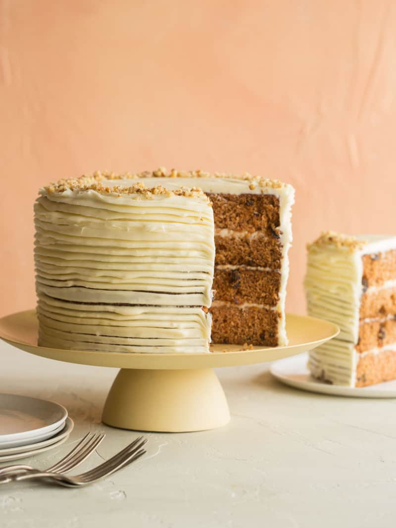 A recipe for carrot cake with cream cheese frosting on a cake pedestal with a slice cut out. The slice is sitting next to the cake on a plate. The cake is three layers.