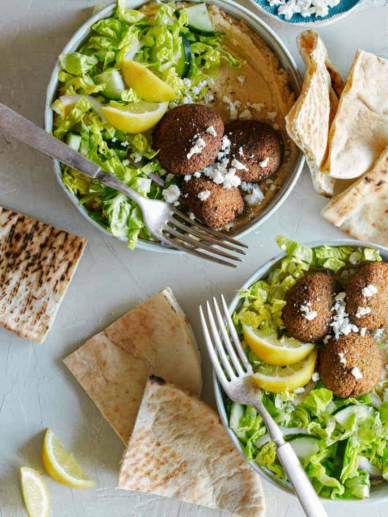 Falafel salad hummus bowls with forks and grilled pita bread.