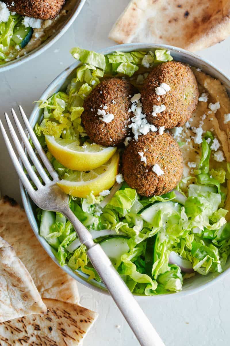 A close up of a falafel salad hummus bowls with a fork.