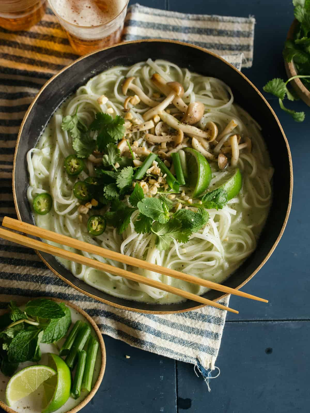 A bowl of green curry noodle soup with chopsticks.