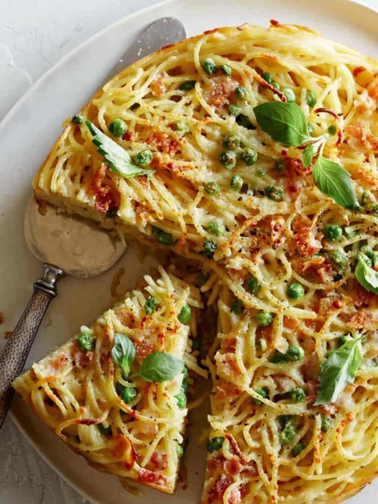 A close up of a sliced carbonara pasta pie with a silver pie server.