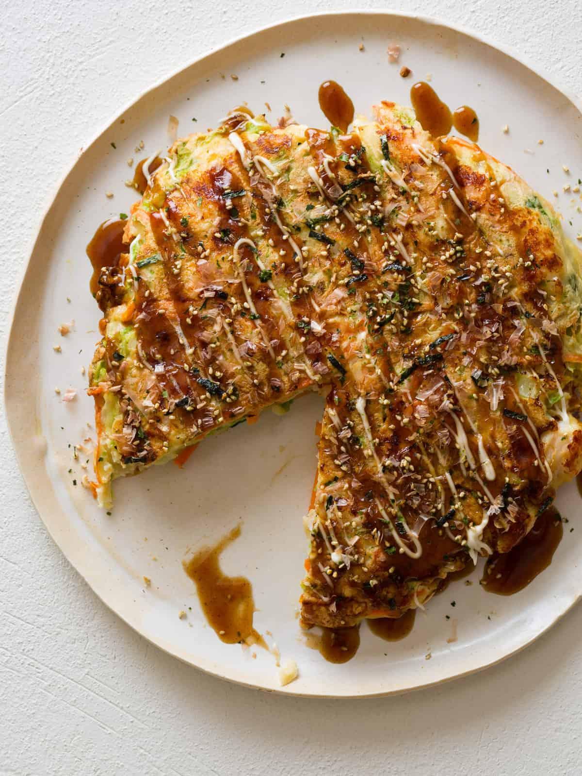 Shrimp okonomiyaki with a slice taken out on a white plate.