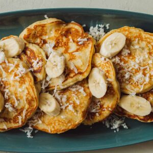 A close up of a plate of coconut banana pancakes with fresh bananas and shredded coconut.