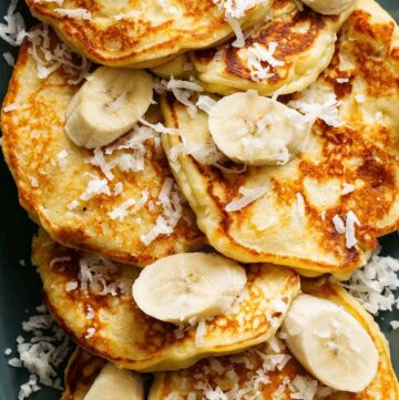 A close up of coconut banana pancakes with fresh bananas and coconut flakes.