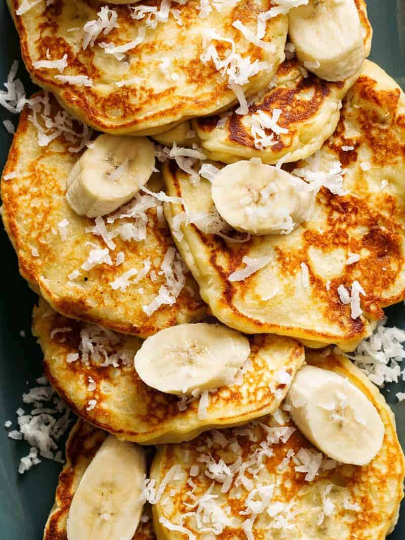 A close up of coconut banana pancakes topped with fresh bananas and shredded coconut.