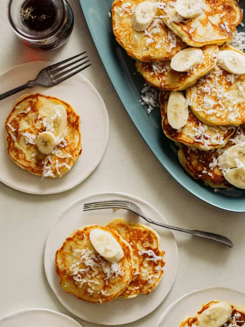 A platter of coconut banana pancakes with servings on small plates and forks.
