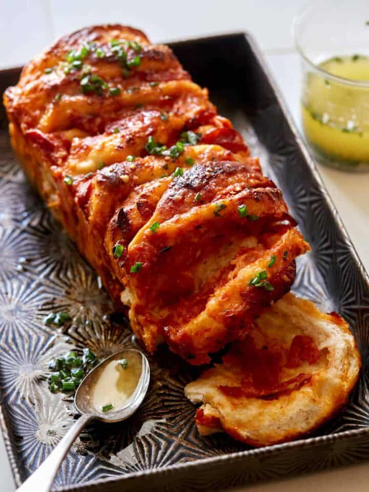 Pizza pull apart bread with a spoon and garlic herb butter.