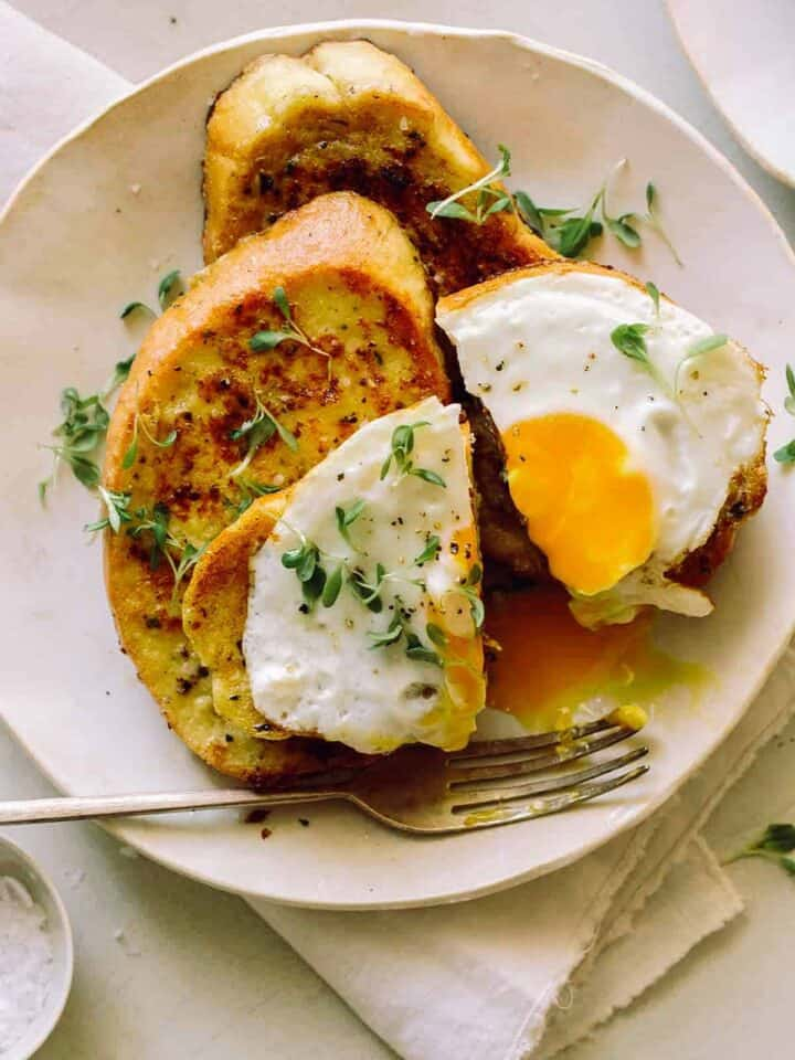 A plate of savory herb french toast with a broken egg yolk and a fork.