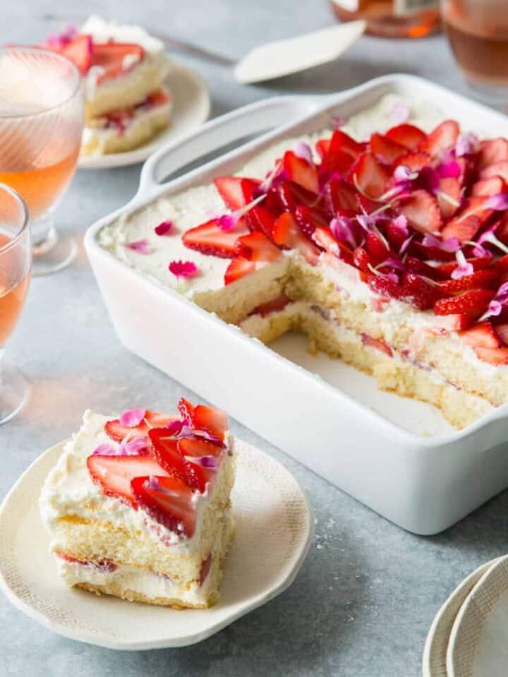 A sliced strawberry tiramisu with a piece on a small plate, a Valentines day dessert.