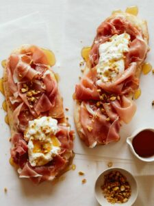 Simple charcuterie flatbreads with honey on the side.