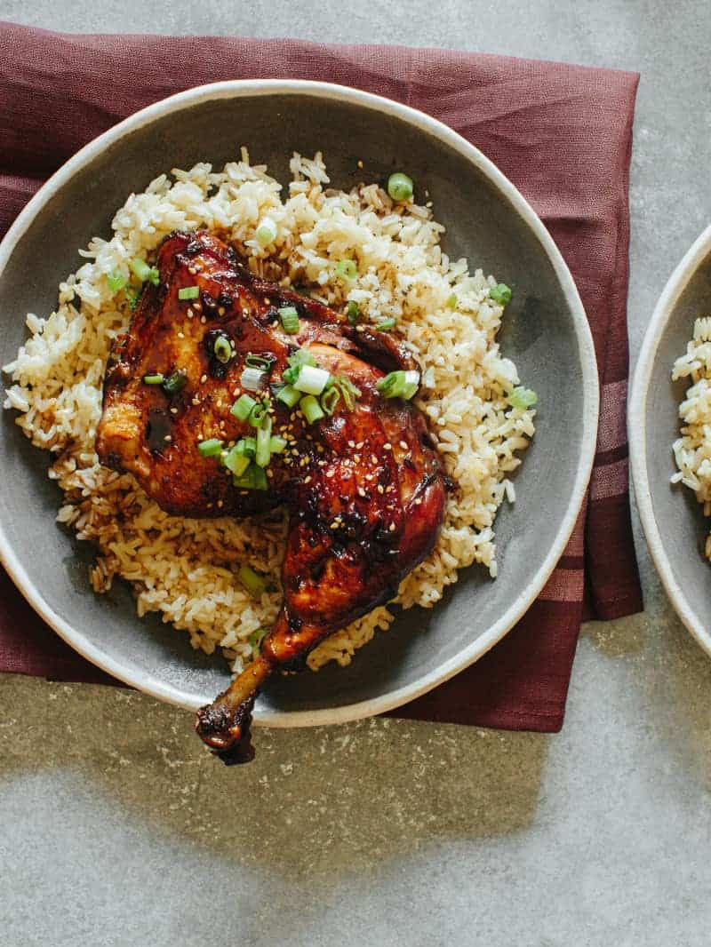 Garlic and Ginger Braised Chicken recipe on a plate over a bed of brown rice.