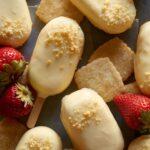 White chocolate dipped no bake strawberry cheesecake bars with fresh strawberries.