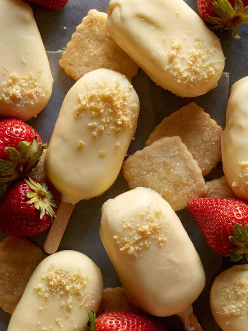 White chocolate dipped no bake strawberry cheesecake bars with fresh strawberries.