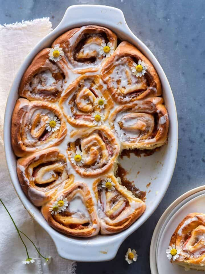 An baking dish of strawberry cinnamon rolls with chamomile and vanilla glaze with one removed.