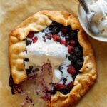 A sliced mixed berry galette with ice cream on the side and on top.