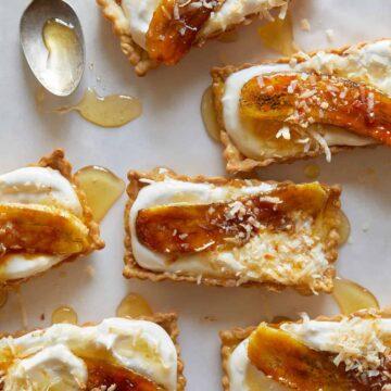 Banana, coconut, and honey cream tarts with a spoon.