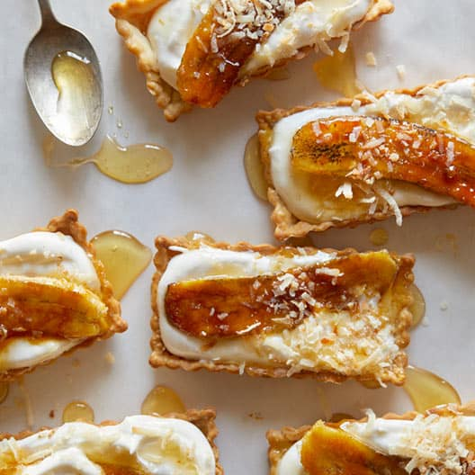 Rectangular banana coconut honey cream tarts with a spoon and honey.