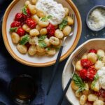 Bowls of caprese gnocchi with cheese, a drink, and forks.