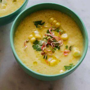 Sweet Corn Gazpacho recipe in a bowl on a counter.