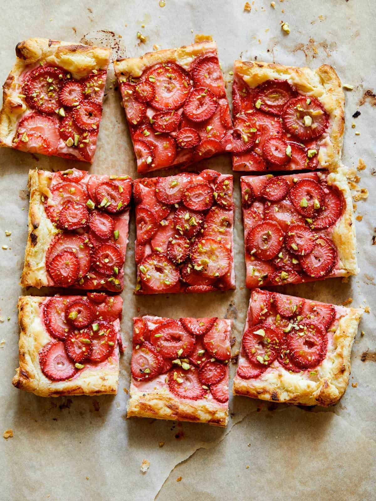 Strawberry Tart with pistachios on a parchment sheet.