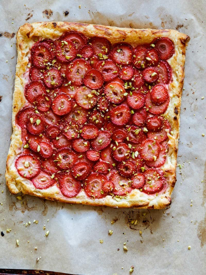 A strawberry tart right out of the oven  on a piece of parchment.