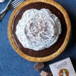 A whole chocolate cream pie with forks and chocolate.