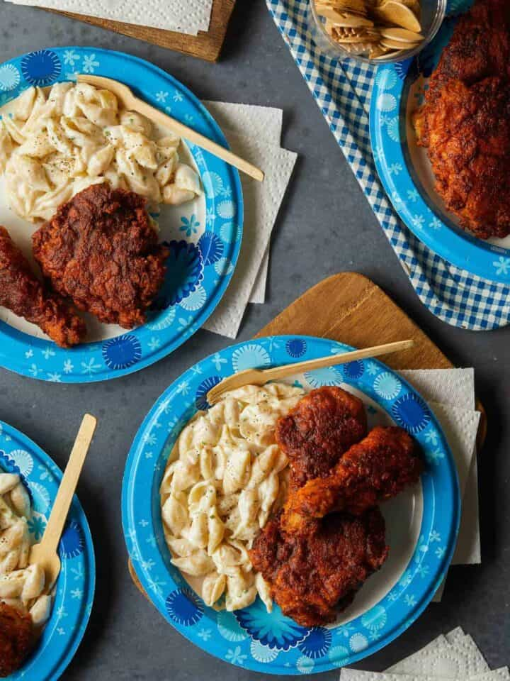 Dixie paper plates of Nashville hot chicken with mac and cheese and disposable wood forks.