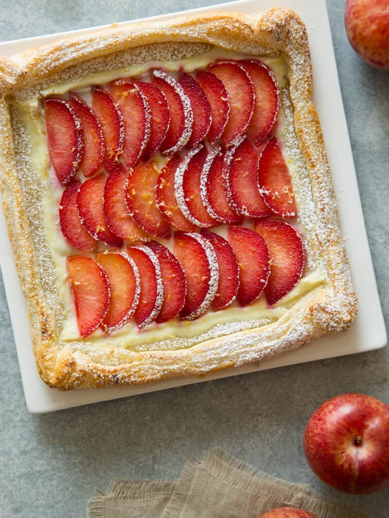 A stone fruit tart on a square plate.