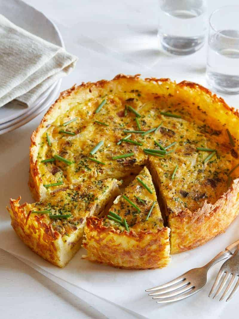 A sliced bacon, cheddar, and chive quiche with hash brown crust.