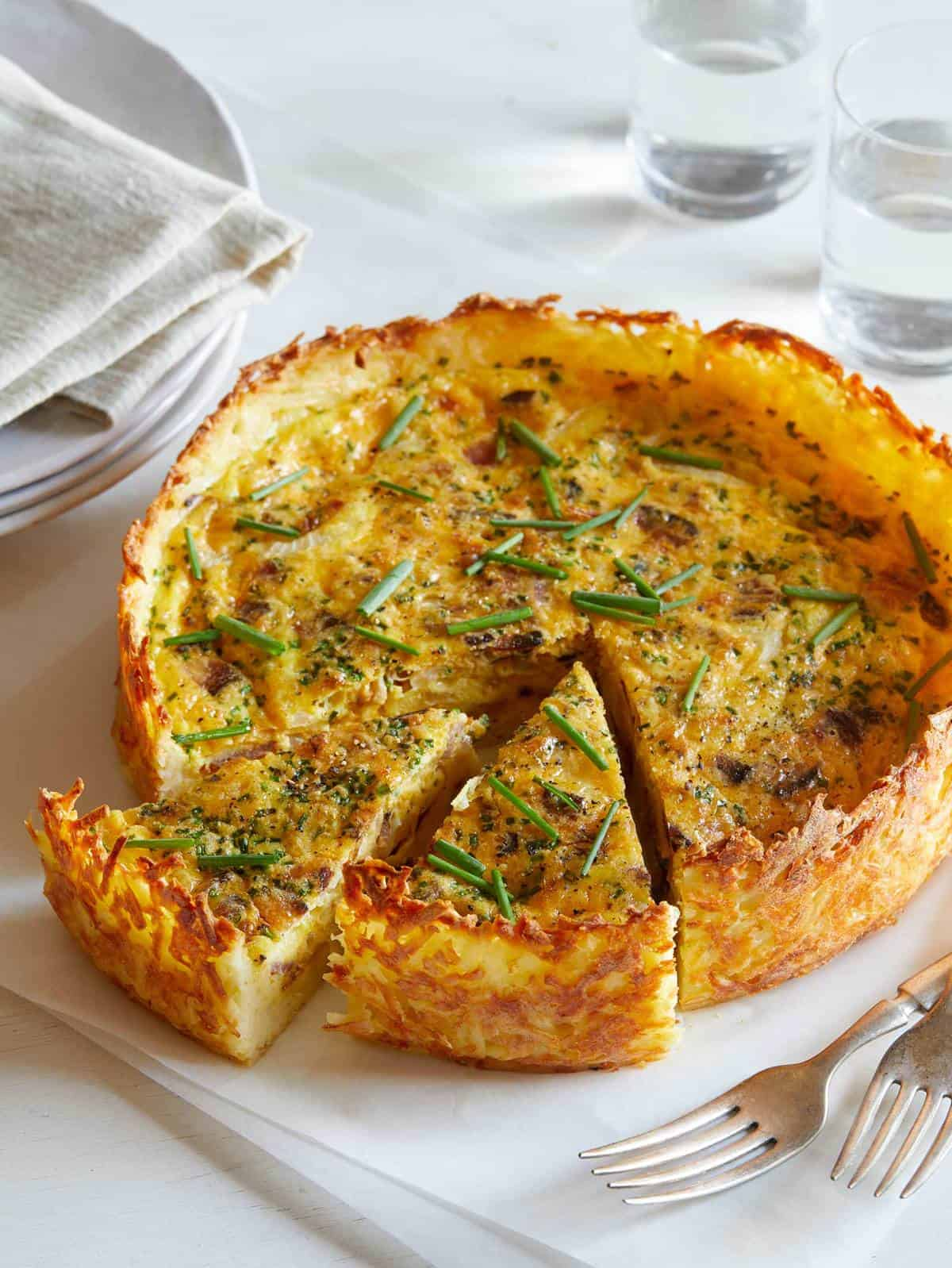 A baon and onion quiche with a hash brown crust on a platter with two slices out.