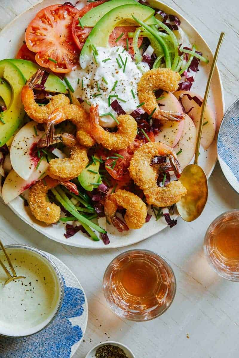 A plate of coconut shrimp summer salad with dressing and drinks on the side.